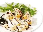 白いお皿に盛り付けられたパルミジャーノとリーフにバルサミコ酢がかかっている写真